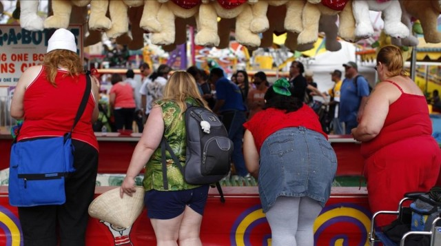 Fairgoers play a carnival game at the San Diego County Fair in Del Mar California in this June 29 2011 file photo To match Special Report OBESITY-WHO INDUSTRY REUTERS Mike Blake Files UNITED STATES - Tags SOCIETY HEALTH FOOD BUSINESS OBESIDAD SOBREPESO EEUU AMERICA AMERICANOS